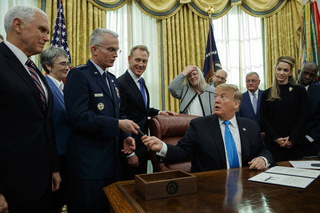 "President Donald Trump hands a pen to Air Force Gen. Paul Selva after signing ""Space Policy Directive 4"" in the Oval Office of the White House, Tuesday, Feb. 19, 2019, in Washington. (AP Photo/ Evan Vucci)"