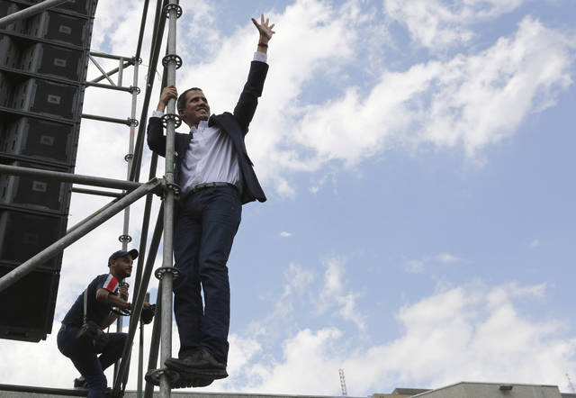 Venezuelan Congress President Juan Guaido, an opposition leader who declared himself interim president, waves to supporters from the stage's scaffolding after speaking to supporters during a rally demanding the resignation of Venezuelan President Nicolas Maduro in Caracas, Venezuela, Monday, March 4, 2019. The United States and about 50 other countries recognize Guaido as the rightful president of Venezuela, while Maduro says he is the target of a U.S.-backed coup plot. (AP Photo/Fernando Llano)