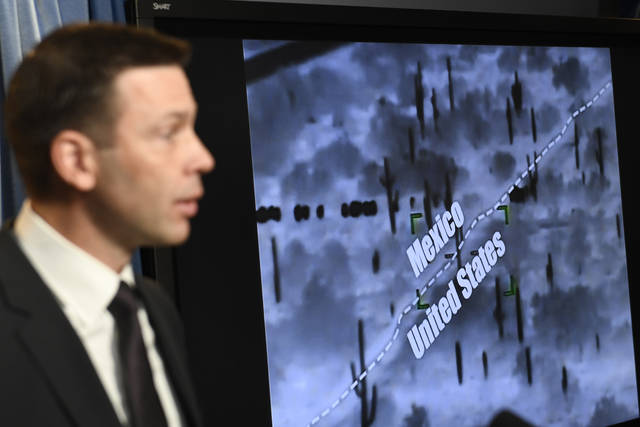 With surveillance footage in the background, U.S. Customs and Border Patrol Commissioner Kevin McAleenan speaks during a news conference in Washington, Tuesday, March 5, 2019. (AP Photo/Susan Walsh)