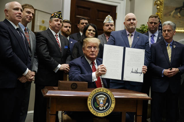 "President Donald Trump shows off an executive order on a ""National Roadmap to Empower Veterans and End Veteran Suicide,"" in the Roosevelt Room of the White House, Tuesday, March 5, 2019, in Washington. (AP Photo/ Evan Vucci)"