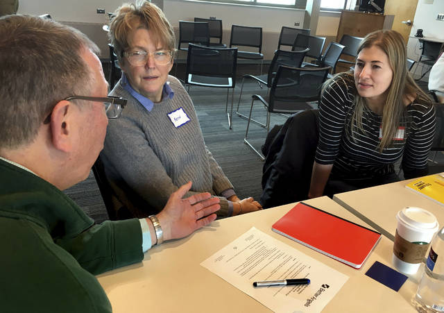 In a  Jan. 26, 2019 photo, Beth Hannan, center, wearing a blue name tag for Democrats, and Emily Helgeson, right, with a red name tag for Republicans, listen to a presenter at the Better Angels meeting at the Inver Glen Library in Inver Grove Heights, Minn. The group encourages conversations between liberals and conservatives. (Bob Shaw/Pioneer Press via AP)