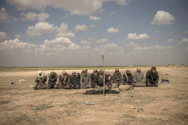 In this Wednesday, March 6, 2019, photo, men pray at a reception area for people evacuated from the last shred of territory held by Islamic State militants, outside Baghouz, Syria. (AP Photo/Gabriel Chaim)