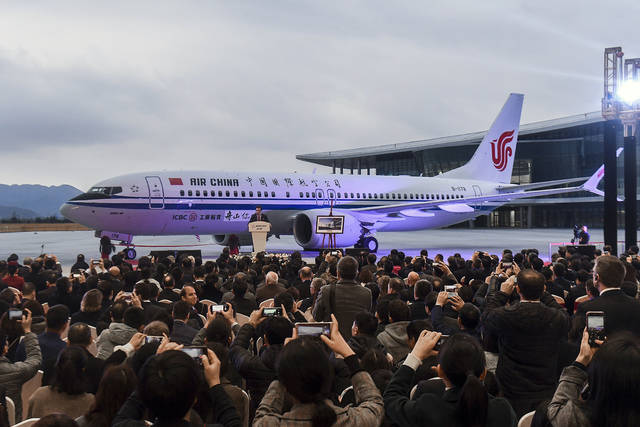 In this Dec. 15, 2018, photo released by Xinhua News Agency, invited guests take photos of the Boeing 737 Max 8 airplane deliver to Air China during a ceremony at Boeing Zhoushan 737 Completion and Delivery Center in Zhoushan, east China's Zhejiang Province. China's civilian aviation authority has ordered all Chinese airlines to ground their Boeing 737 Max 8 planes on Monday, March 11, 2019 after one of the aircraft crashed in Ethiopia. The authority said the one-day action was made out of safety concerns because the crash was similar to one in Indonesia last year. (Xu Yu/Xinhua via AP)