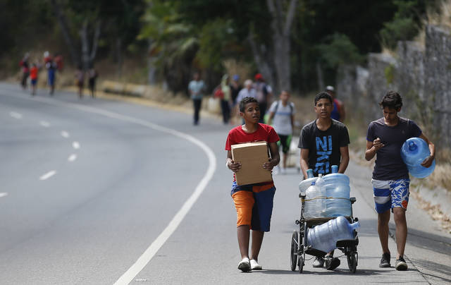 Youths carry empty containers which they'll use to collect water, during rolling blackouts affecting the water pumps in people's homes and apartment buildings, in Caracas, Venezuela, Sunday, March 10, 2019.  Venezuelans reached new levels of desperation Sunday as the country's worst blackouts took their toll, gathering in larger numbers than usual at springs in the mountains of Caracas to collect water and scrounging for scarce cash to pay for food in the few shops that were open.  (AP Photo/Eduardo Verdugo)
