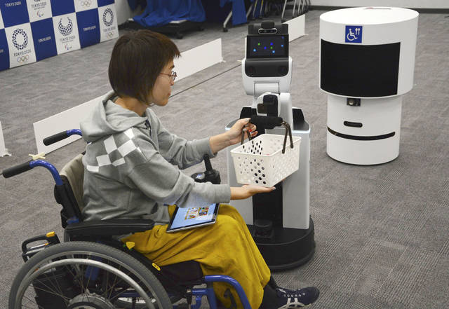 A robot passes a basket containing drinks to a woman in wheelchair during an unveiling event in Tokyo Friday, March 15, 2019. Organizers on Friday showed off robots that will be used at the new National Stadium to provide assistance for fans using wheelchairs. (Kyodo News via AP)