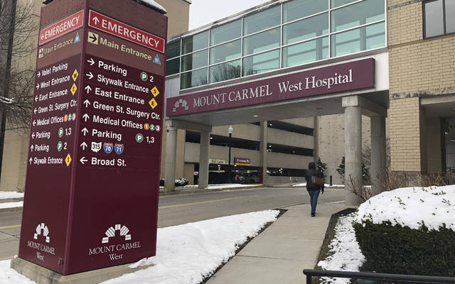 FILE - In this Jan. 15, 2019 file photo, the main entrance to Mount Carmel West Hospital is shown in Columbus, Ohio. The Ohio hospital system where an intensive-care doctor is accused of ordering painkiller overdoses for dozens of patients says it has put more employees on leave and changed key leaders at the hospital where nearly all those deaths occurred. Mount Carmel Health System said Wednesday, March 13 that 48 nurses and pharmacists under review have been reported to regulatory boards. It says 30 are on leave, and 18 no longer work there. The doctor was fired in December. (AP Photo/Andrew Welsh Huggins, File)