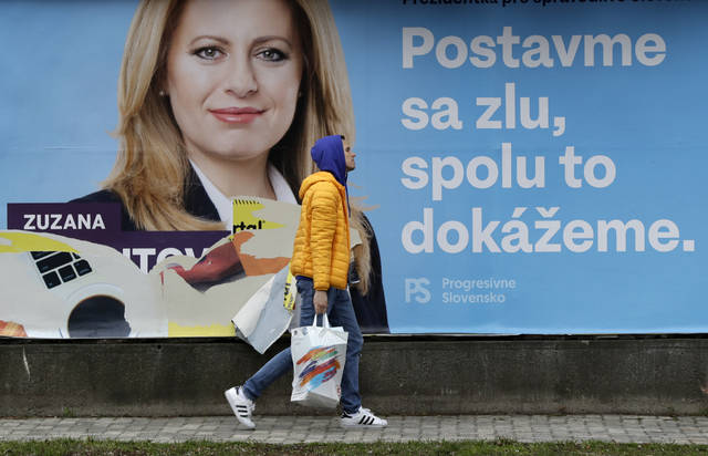 """A man walks past a campaign poster for Zuzana Caputova in Bratislava, Slovakia, Friday, March 15, 2019. Caputova is one of the favorite candidates to succeed Slovakia's President Andrej Kiska in the upcoming election. Slovakia holds the presidential election on Saturday, March 16, 2019. The poster reads: """"Let's stand against evil, together we can make it."""" (AP Photo/Petr David Josek)"""