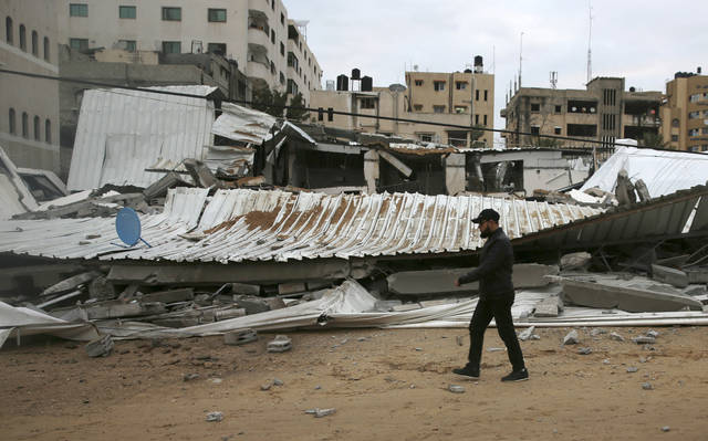 A Palestinian inspects the damage of destroyed building belongs to Hamas ministry of prisoners hit by Israeli airstrikes in Gaza City, early Friday, March 15, 2019. Israeli warplanes attacked militant targets in the southern Gaza Strip early Friday in response to a rare rocket attack on the Israeli city of Tel Aviv, as the sides appeared to be hurtling toward a new round of violence. (AP Photo/Adel Hana)