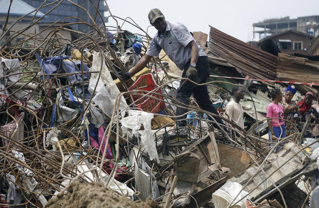 Government officials from Standard Organisation of Nigeria examine materials used in constructing the building that collapsed in Lagos, Nigeria, Thursday March 14, 2019. A Nigerian official says search efforts have been halted a day after a school building collapsed in Lagos with an unknown number of children inside.(AP Photo/Sunday Alamba