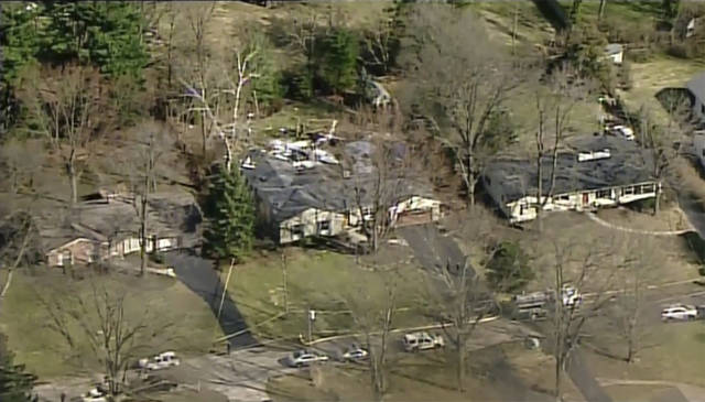 This image provided by WKRC-TV shows emergency crews responding to a plane crash into a house in Madeira, Ohio, Tuesday, March 12, 2019. Madeira's fire chief, Steve Ashbrock, says the plane crashed into a family room at the back of the home, then went nose-first into the back yard.  (WKRC-TV via AP)