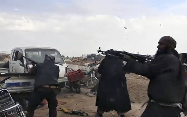 This frame grab from video posted online Monday, March 18, 2019, by the Aamaq News Agency, a media arm of the Islamic State group, shows Islamic State fighters firing their weapons during clashes with the U.S.-backed Syrian Democratic Forces (SDF) fighters, in Baghouz, the Islamic State group's last pocket of territory in Syria. U.S.-backed Syrian forces fighting the Islamic State group announced Tuesday they have taken control over an encampment in an eastern Syrian village where IS militants have been besieged for months, refusing to surrender. (Aamaq News Agency via AP)