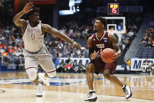 FILE - In this March 14, 2018, file photo, Texas Southern's Donte Clark (1) eyes the basket against North Carolina Central's Larry McKnight Jr. (0) during the first half of a First Four game of the NCAA men's college basketball tournament in Dayton, Ohio. The First Four has become a reward and showcase for Historically Black College and Universities, the group of schools that predate the integration, that usually do not get to play in the national spotlight without being a tasty opening-round appetizer for a No. 1 seed. (AP Photo/John Minchillo, File)