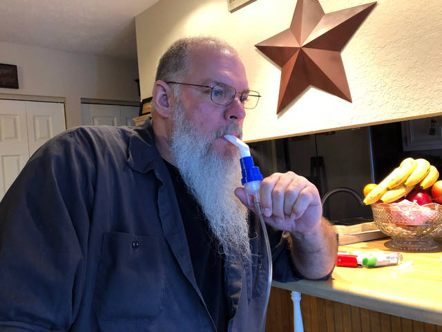 Retired coal miner John Robinson uses a nebulizer during his daily breathing treatments for black lung disease on Thursday, Jan. 24, 2019 in Coeburn, Va. Robinson was 47 when he was diagnosed with black lung disease, part of a new generation of black lung sufferers who are contracting the deadly disease at younger ages. (AP Photo/Dylan Lovan)