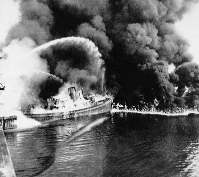 FILE - In this June 25, 1952 file photo, a fire tug fights flames on the Cuyahoga River near downtown Cleveland.  Federal environmental regulators say fish living in the northeastern Ohio river are now safe to eat. The easing of fish consumption restrictions on the Cuyahoga  River was lauded by Republican Gov. Mike DeWine as progress achieved by investing in water quality.(The Plain Dealer via AP)