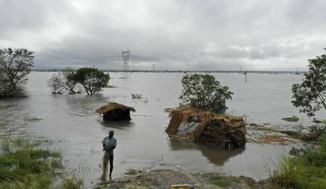 A man stands in flood waters following cyclone force winds and heavy rain near the coastal city of Beira, Mozambique, Wednesday March 20, 2019. Torrential rains were expected to continue into Thursday and floodwaters were still rising, according to aid groups trying to get food, water and clothing to desperate survivors. It will be days before Mozambique's inundated plains drain toward the Indian Ocean and even longer before the full scale of the devastation is known. (Josh Estey/CARE via AP)