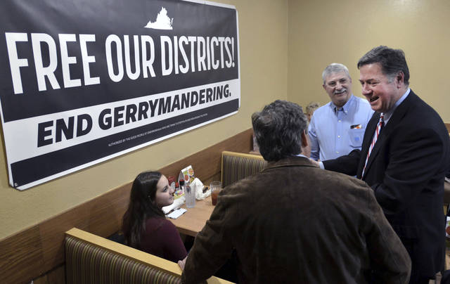 FILE- In this Feb. 2, 2019, file photo former Virginia Governor and U.S. Sen. George Allen, right, talks with supporters during a stop in Bristol, Va. Allen was on a five-city town hall tour of Virginia to discuss the need for nonpartisan and transparent redistricting reform during this year's General Assembly session. In Vermont, a commission submits plans for state House and Senate districts to the state Legislature, which can approve or change them. (David Crigger/Bristol Herald Courier via AP, File)