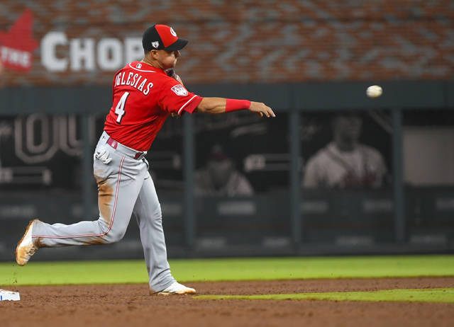 Cincinnati Reds shortstop Jose Iglesias throws out Atlanta Braves' Matt Joyce at first base for a double play during the fifth inning of an exhibition baseball game on Monday, March 25, 2019, in Atlanta. (AP Photo/John Amis)