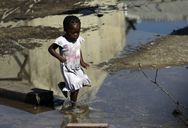 "A young girl walks into the water outside a school setup as a displacement centre at Inhamizua, outside of Beira, Mozambique, Tuesday, March 26, 2019. Cyclone-ravaged Mozambique faces a ""second disaster"" from cholera and other diseases, the World Health Organization warned on Tuesday, while relief operations pressed into rural areas where an unknown number of people remain without aid more than 10 days after the storm. (AP Photo/Themba Hadebe)"