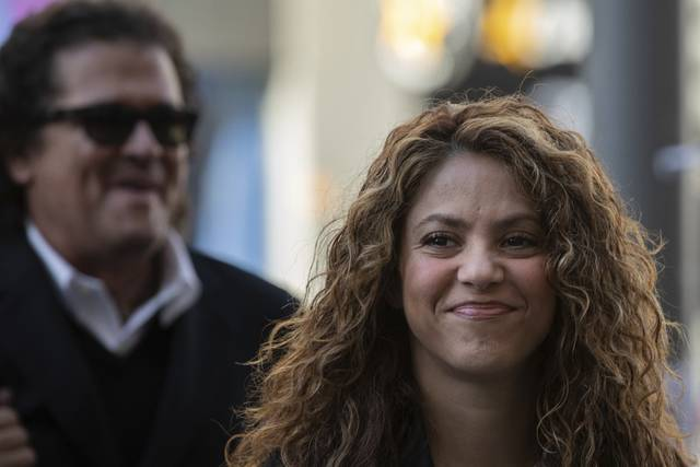 "Colombian singers Shakira, right, and Carlos Vives, background, arrive at court in Madrid, Spain, Wednesday, March 27, 2019. Shakira and Vives have previously rejected allegations made by a Cuban-born singer and producer that they had plagiarized his work in their award-winning music hit ""La Bicicleta"". (AP Photo)"