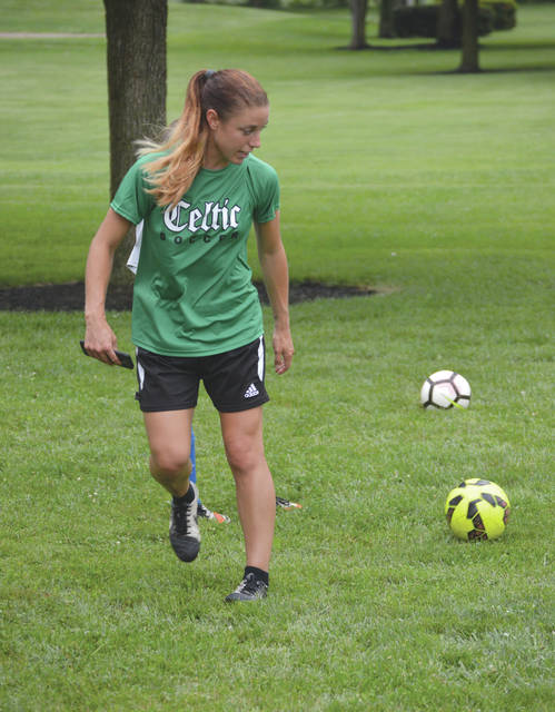 Head coach Abby Pearson demonstrates a passing technique to her BSA Celtic U12 girls soccer players, July 13, during a rainy soccer practice at Rotary Park in Beavercreek.