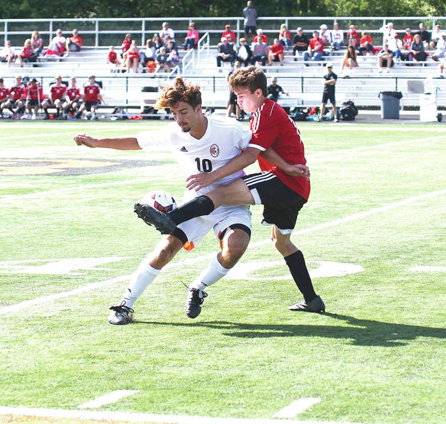 Barb Slone | News-Current Columbus St. Charles sophomore defender Tyler Cunningham kicks the ball in front of Beavercreek's senior forward Evan Williams, during Saturday's Sept. 9 boys high school soccer match on Frank Zink Field in Beavercreek. The two teams played to a 1-all tie.