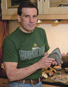 Chuck Ciampaglio holds a tooth from the prehistoric shark megalodon.