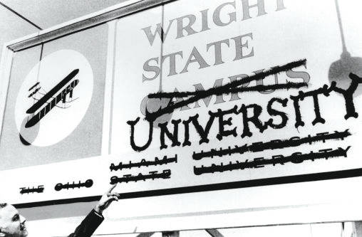 President Brage Golding pointing at the former Wright State Campus sign.