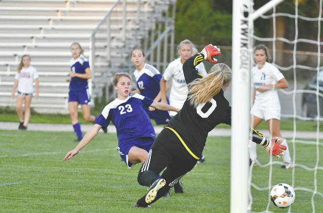 Bellbrook sophomore forward Bailey Sedlak (23) slides to kick a shot past Carroll goaltender Eliza Graham (0) for the only goal of the match Sept. 16 at Carroll High.
