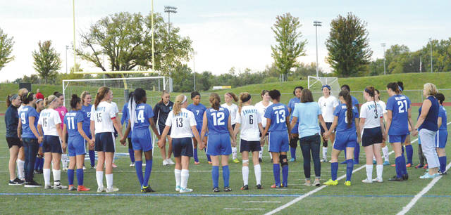 Members of the Xenia Legacy Christian and Yellow Springs girls high school soccer teams gather together for a post-game prayer, after a recent soccer match at the Athletes In Action Sports Complex in Xenia.