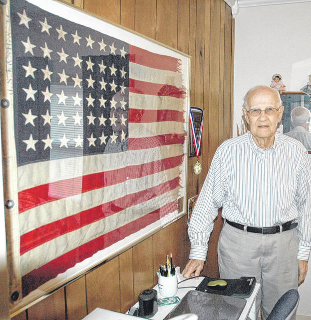 Scott Halasz | News-Current Beavercreek resident Baylor Kirk shows off the flag that flew over the USS Loy during World War II. He was given the flag and takes it to the yearly reunion.