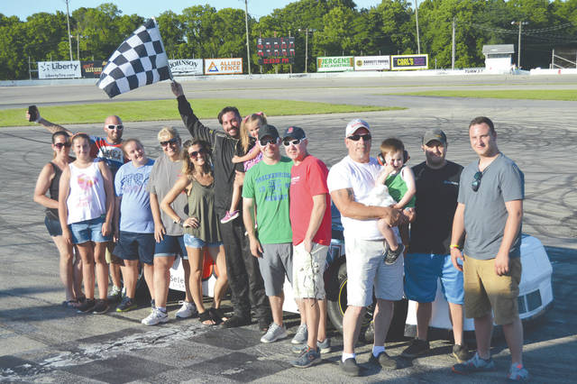 Jamie Sites waves the checkered flag, as his family and crew celebrate his win in the 25-lap Sport Stock feature, July 8 at the Sunday Slam stock car racing event at Kil-Kare Raceway. Sites was also runner up in Sunday afternoon's Modifed race.