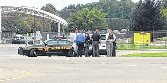 Scott Halasz | Greene County News Law enforcement officials huddle outside a gate to Wright-Patterson Air Force Base as an active-shooter incident is investigate.