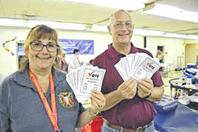Submitted photo Beavercreek Township Fire Department Auxiliary organizer Pat Cochran and Peace Lutheran Church blood drive coordinator Dan Jessup hold ballots from last year's drive.