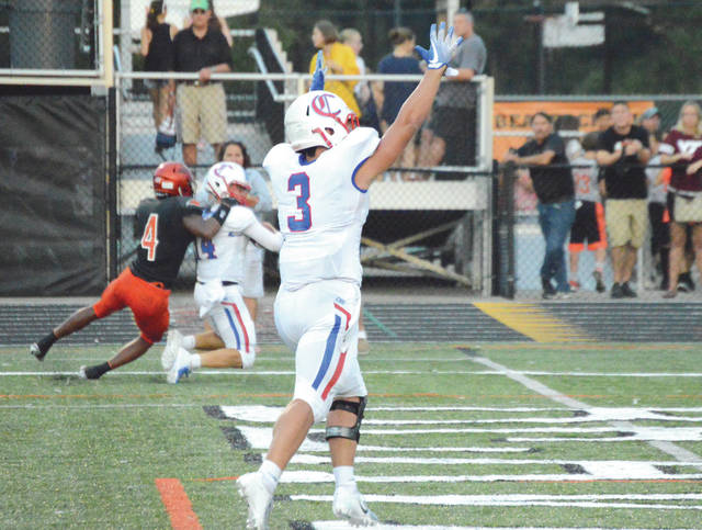 Carroll's Jon Lajeunesse (3) signals the touchdown as Patriots quarterback Trent Fox scores the team's first touchdown of the first half, in an eventual come-from-behind win over host Beavercreek, Aug. 31 at Frank Zink Field.