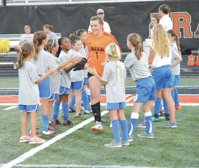 Beavercreek senior goalie/ co-captain Lauren Galloway, smiles as she runs through a corridor of Celtic youth soccer ball girls prior to Wednesday's Greater Western Ohio Conference girls high school soccer match with visiting Springfield.