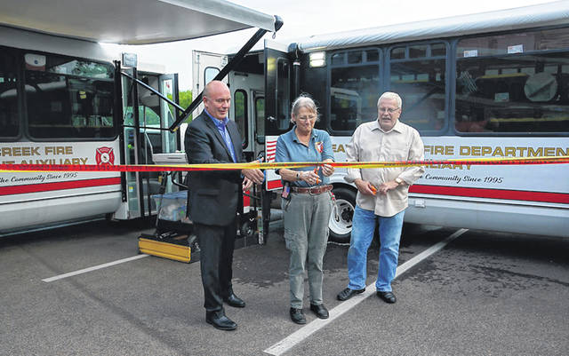 Submitted Photo The Beavercreek Fire Department received new auxiliary buses. Pictured from the left: Tom Kretz Beavercreek Township Trustee; Kate Hone Auxiliary President; Bob Stone Mayor during a special the ribbon cutting for the Beavercreek Fire Department.