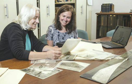Dawne Dewey and Toni Vanden Bos examine photos from the Wright Brothers Collection in the Special Collections and Archives in Dunbar Library.