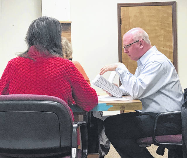 Anna Bolton | Greene County News John Caupp, chair of Greene County Board of Elections, looks through a bundle of unopened absentee ballots at the Nov. 20 meeting.