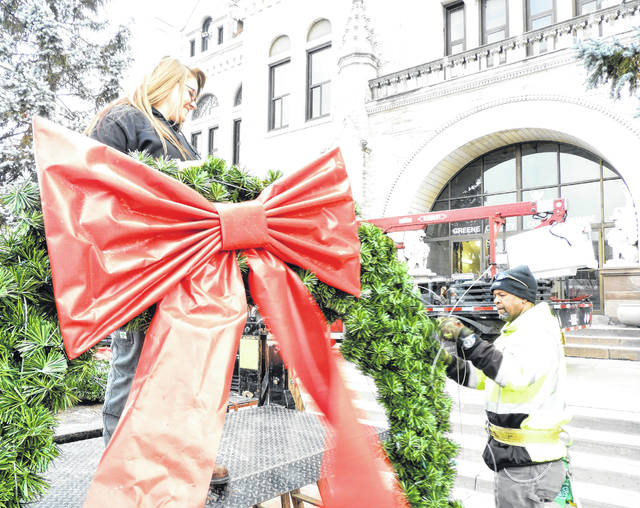 Photos courtesy of GCP&T Greene County Parks & Trails' Brianna Trangenstein and Grounds Supervisor Dave Dudgeon move a wreath from the truck before hanging it at the Greene County courthouse. The Greene County Highway Department loaned the bucket truck to the maintenance team to hang the wreaths.