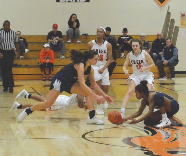 Beavercreek sophomore Trinity Bean is obscured as she dives for a loose ball, Dec. 22 at Beavercreek High.