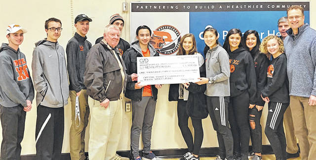 Submitted photo Greene Giving contributed $1,300 to the 2018 Resolution Run. Pictured here with members of the Beavercreek High School Cross Country team's Captains and Leadership Council are: Greene Giving Board Members Paul Newman (4th from left), Edward Marrinan (2nd from right), and Jamie Hensley (far right).