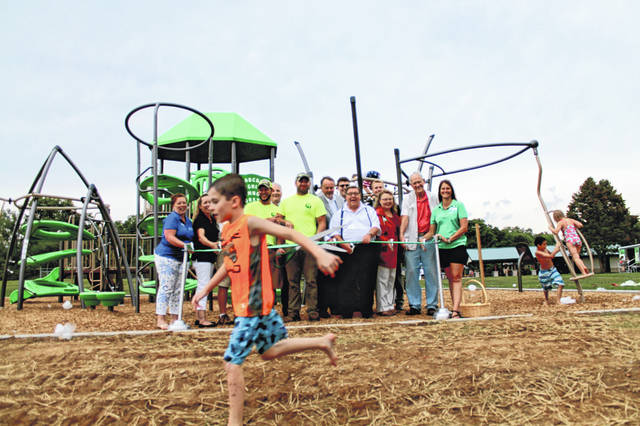 Local officials laugh as a couple playground-testers run through the shot during the ribbon cutting for the playground, renovated picnic shelter and two new sets of basketball goals. Funds for the new playground came from a matching grant from GameTime Playground Systems and the Ohio Parks & Recreation Association, with support from DWA Recreation.