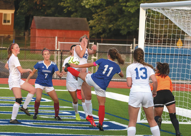 Senior co-captain Alaina Casey (11) kicks the ball over a Clinton-Massie defender and goalie to score the first Carroll girls varsity soccer goal at Jim Spoerl-Steve Bartlett Field at Carroll High School.