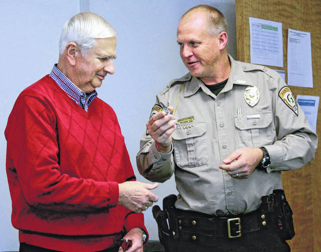 Greene County Parks & Trails Chief Ranger Brady Smith gives a challenge coin to Greene County Park District Commissioner John A. Finlay.