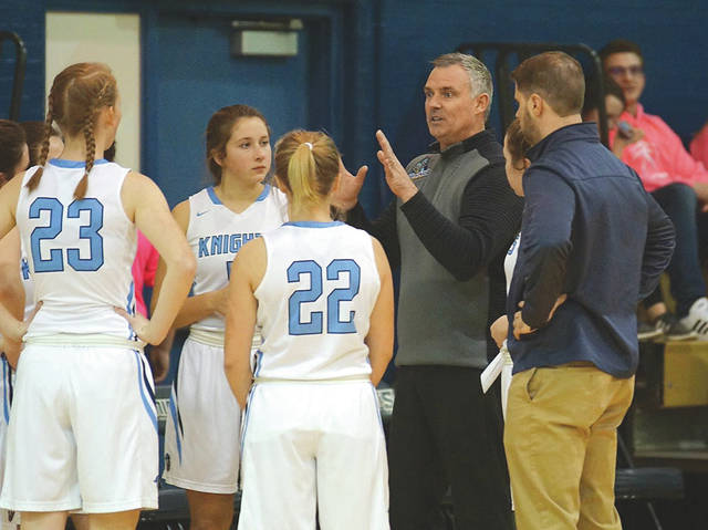 Legacy Christian Academy girls varsity basketball coach Mark Combs talks strategy during a timeout in Thursday's home game against Miami Valley School. The Knights won the game, 50-10, which was Comb's 100th career win as head basketball coach.