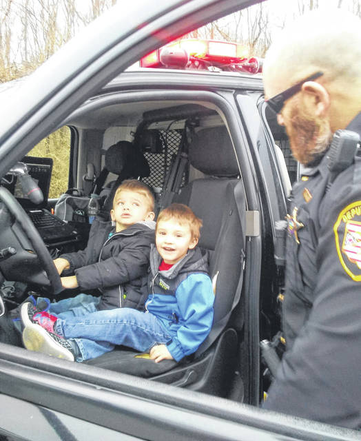 Photos courtesy Sharon Ewry While out with her four grandchildren, Sharon Ewry noticed the parked vehicle of Sheriff's Deputy Richard Jones. She stopped and Jones offered to give the kids a tour of his cruiser. He gave them tattoos, bracelets, and magnets. Pictured with Jones are Bryce Elam (black coat), and Morgan (blue coat) and Cecelia Ewry (pink coat).