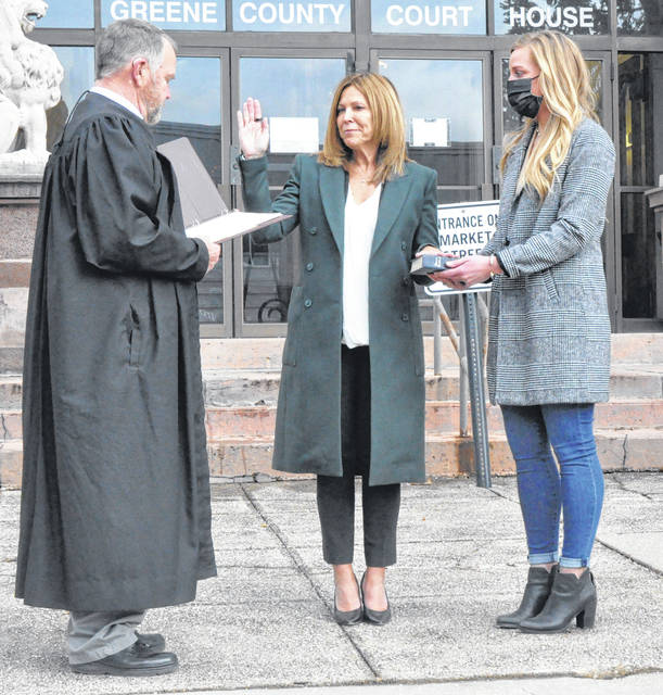 Photos by Scott Halasz | Greene County News Cynthia Martin (middle) is sworn in by Greene County Common Pleas Domestic Relations Court Judge Steven Hurley. Martin was elected to replace the retiring Hurley and is the first female elected to the county court. Holding the Bible is daughter Christina Martin.