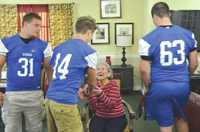 Edna Adams, of the Doug Adams Trust Fund, particularly liked Xenia quarterback No. 14 Christian Severt's hairstyle, during a morning presentation by members of the Xenia High football team at the Elmcroft Assisted Living Center in Xenia.