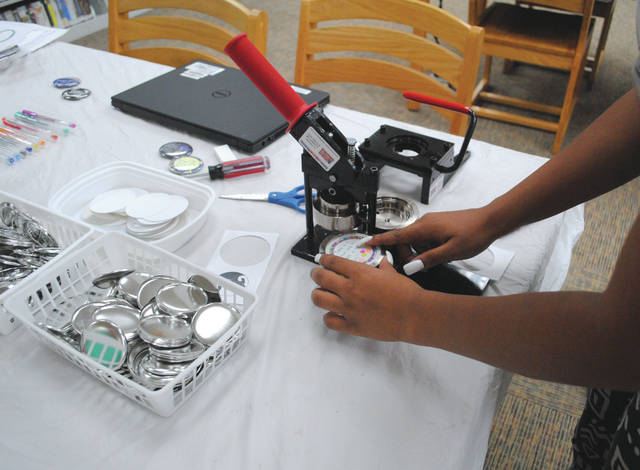 Whitney Vickers | Greene County News The Fairborn Library invited community members to create buttons June 29 on a drop-in basis. Participants could pick out or create their own design, place it into the button-making machine and walk out with their own creation.