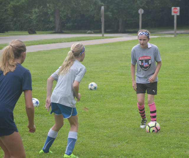 A BSA Celtic U12 soccer player looks to pass around a pair of teammates, during a practice session July 13 at Rotary Park in Beavercreek.